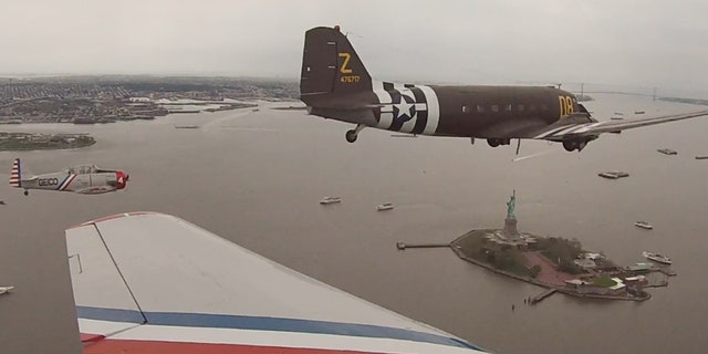 The Geico Skytypers and a Douglas C-47 military transport plane fly by the Statue of Liberty Thursday.