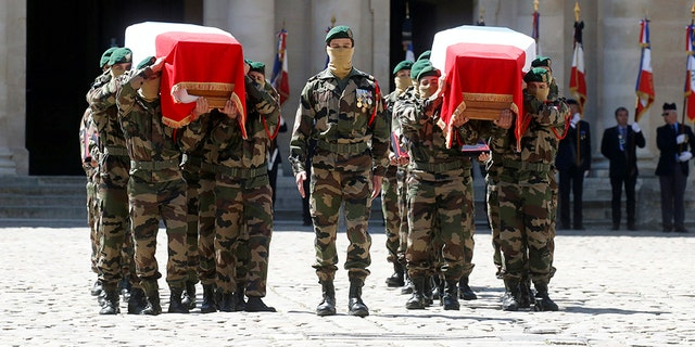 Special forces soldiers carry the flag-drapped coffins of late special forces soldiers Cedric de Pierrepont and Alain Bertoncello, who were killed in a night-time rescue of four foreign hostages including two French citizens in Burkina Faso last week, during a national tribute at the Invalides, in Paris, Tuesday, May 14, 2019. France is honoring two special forces officers killed in an operation that freed four hostages held in Burkina Faso.