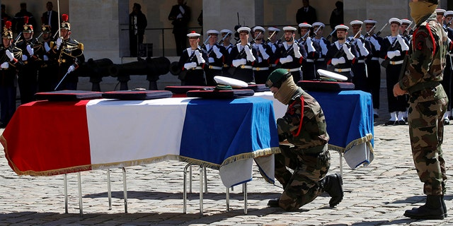 A special forces soldier places a rope between the flag-drapped coffins of late special forces soldiers Cedric de Pierrepont and Alain Bertoncello, who were killed in a night-time rescue of four foreign hostages including two French citizens in Burkina Faso last week, during a national tribute at the Invalides, in Paris, Tuesday, May 14, 2019. France is honoring two special forces officers killed in an operation that freed four hostages held in Burkina Faso.