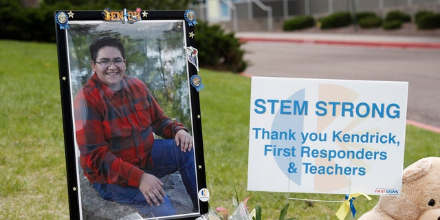 A photograph of student Kendrick Castillo stands amid a display of tributes outside the STEM School Highlands Ranch a week after the attack on the school that left Castillo dead and others injured, Tuesday, May 14, 2019, in Highlands Ranch, Colo.