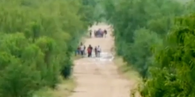 """Migrants are seen walking down a road at a portion of the U.S.-Mexico border one top official is calling """"ground zero"""" for illegal crossings."""