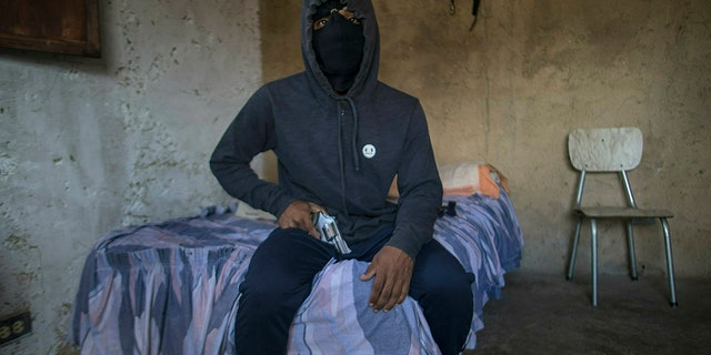 "A masked gangster who goes by the nickname ""El Negrito"" poses for a portrait with his gun inside his gang's safe-house in the Petare slum of Caracas, Venezuela, Monday, May 13, 2019. The 24-year-old, who says he's lost track of his murder count, is quick to gripe about how Venezuela's failing economy is cutting into his profits and has considered leaving the trade in Venezuela and emigrating. (AP Photo/Rodrigo Abd)"