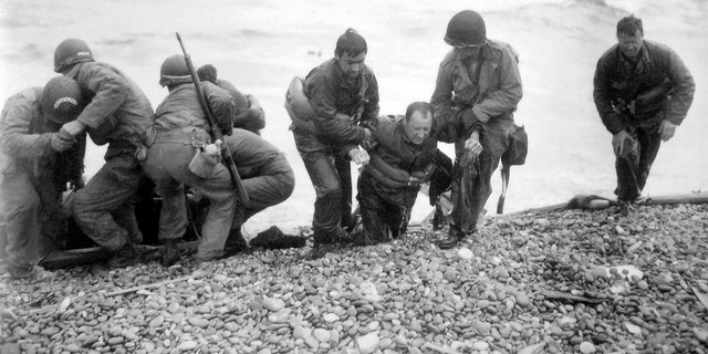 FILE - In this file photo from June 6, 1944, members of an American landing unit help their comrades ashore during the Normandy invasion. The men reached the zone code-named Utah Beach, near Sainte- Mere-Eglise, on a life raft after their landing craft was hit and sunk by German coastal defenses. (Louis Weintraub/Pool Photo via AP, File)