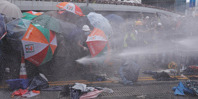 Protesters are hit by police water cannon during a demonstration against a proposed extradition bill in Hong Kong, China June 12, 2019. REUTERS/Tyrone Siu - RC12C6522E40