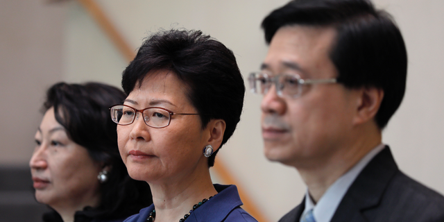Hong Kong Secretary for Security John Lee, right, Hong Kong Chief Executive Carrie Lam, center, and Secretary of Justice Teresa Cheng listen to reporters questions during a press conference in Hong Kong on June 10, 2019.  (AP Photo/Vincent Yu)