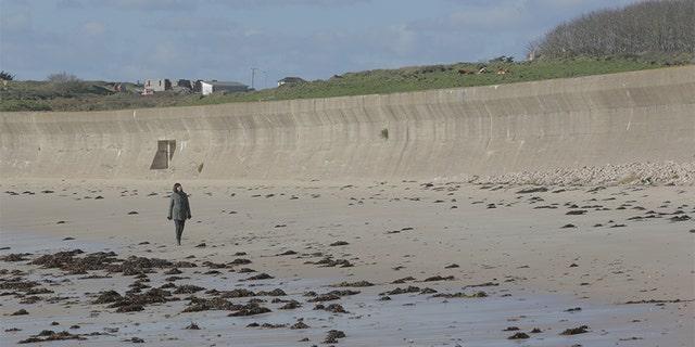 Professor Caroline Sturdy Colls walks along the beach in front of a concrete wall, Alderney.