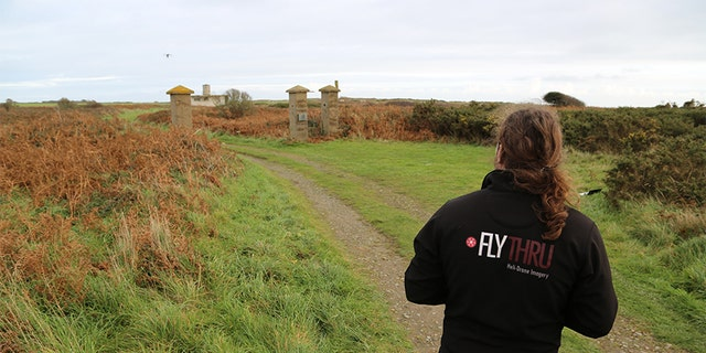 Flying drone over remains of the old gates at Sylt, drone operator in the foreground, Alderney. —SNI/SI Networks L.L.C.