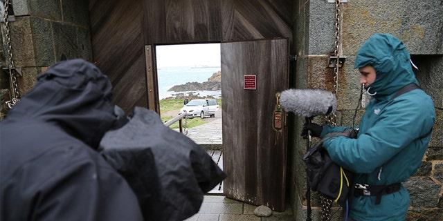 Caroline Sturdy Colls returning to base, Alderney — filming through gate doors. —SNI/SI Networks L.L.C.