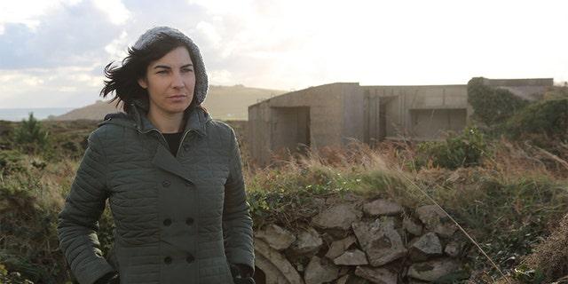 Professor Caroline Sturdy Colls standing next to concrete fortification on Alderney. —SNI/SI Networks L.L.C.