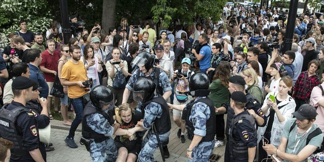Police officers detain a protester during a march in Moscow, Russia, Wednesday, June 12, 2019. Police and hundreds of demonstrators are facing off in central Moscow at an unauthorized march against police abuse in the wake of the high-profile detention of a Russian journalist.