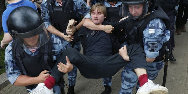Police officers detain a protester during a march in Moscow, Russia, Wednesday, June 12, 2019. Police and hundreds of demonstrators are facing off in central Moscow at an unauthorized march against police abuse in the wake of the high-profile detention of a Russian journalist. More than 20 demonstrators have been detained, according to monitoring group.