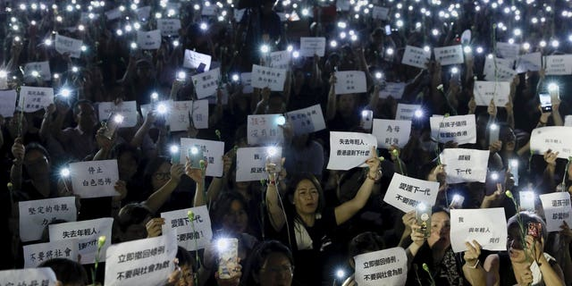 "Hundreds of mothers holding placards, some of which read ""If we lose the young generation, what's left of Hong Kong"", and lit smartphones protest against the amendments to the extradition law in Hong Kong on Friday, June 14, 2019. Calm appeared to have returned to Hong Kong after days of protests by students and human rights activists opposed to a bill that would allow suspects to be tried in mainland Chinese courts."
