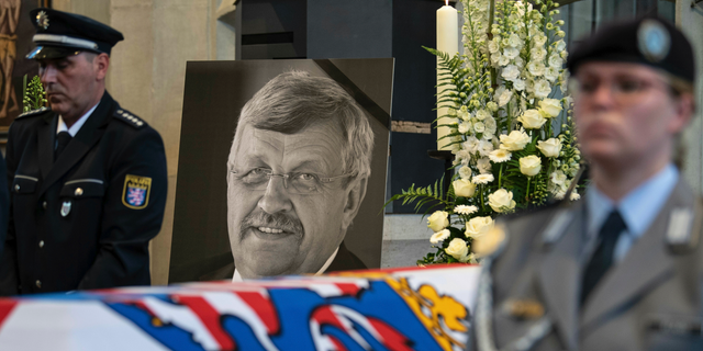 In this June 13, 2019 file photo a picture of Walter Luebcke stands behind his coffin during the funeral service in Kassel, Germany. German authorities say they have arrested a 45-year-old man in connection with their investigation into the slaying of a regional official from Chancellor Angela Merkel's party.