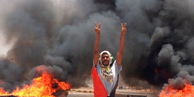 In this Monday, June 3, 2019 file photo, a protester flashes the victory sign in front of burning tires and debris on road 60, near Khartoum's army headquarters, in Khartoum, Sudan, Monday, June 3.