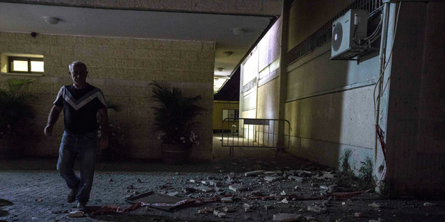 A man stands outside a Jewish religious school in Sderot, Israel, after it was hit by a rocket fired from the Gaza Strip, Thursday, June 13, 2019. (AP Photo/Tsafrir Abayov)
