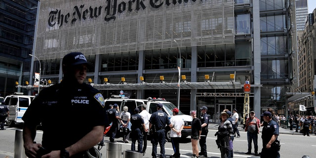 New York Police officers, pictured here taking activists into custody, arrested 70 people during a climate change rally outside of The New York Times building on Saturday.