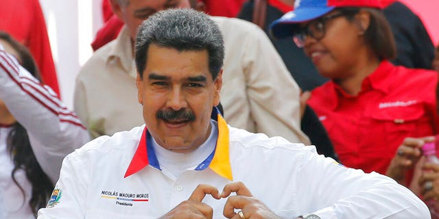 In this May 20 photo, Venezuela's President Nicolas Maduro flashes a hand-heart pitch to supporters outward Miraflores presidential house in Caracas. (AP Photo/Ariana Cubillos)