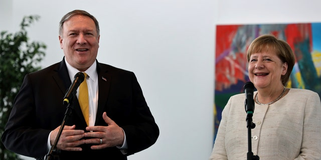 U.S. Secretary of State, Mike Pompeo, left, and German Chancellor Angela Merkel, right, address the media during a joint statement prior to a meeting at the chancellery in Berlin, Germany, Friday, May 31, 2019. (AP Photo/Michael Sohn)