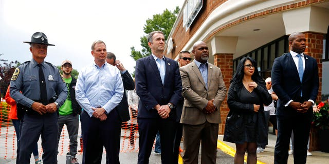 Virginia Gov. Ralph Northam, center, attends a vigil in response to a shooting at a municipal building in Virginia Beach, Va., Saturday morning. A longtime city employee opened fire at the building Friday, with lethal consequences, before police shot and killed him, authorities said. (AP Photo/Patrick Semansky)