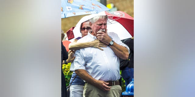 Frank Janes is comforted by his wife, Cathie Janes, during the prayer vigil at Strawbridge Marketplace in response to a shooting at a municipal building in Virginia Beach, Va., Saturday, June 1, 2019. A longtime city employee opened fire at the building Friday before police shot and killed him, authorities said. (Daniel Sangjib Min/Richmond Times-Dispatch via AP)
