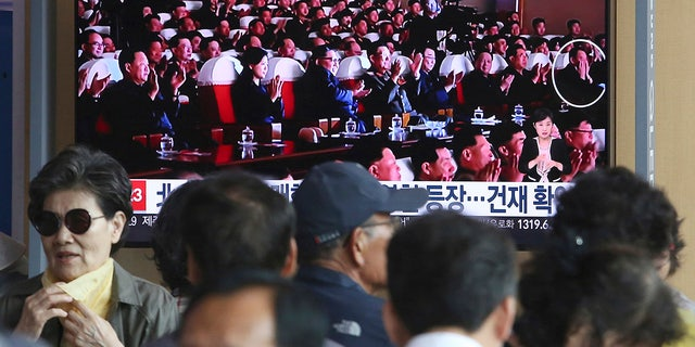 People watch a TV screen showing an image of North Korean leader Kim Jong Un, third from left, and senior North Korean official Kim Yong Chol, right, in a musical performance by the wives of Korean People's Army officers in North Korea during a news program at the Seoul Railway Station in Seoul, South Korea.