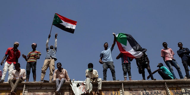 FILE - In this May 2, 2019, file photo, Sudanese protesters wave national flags at the sit-in outside the military headquarters, in Khartoum, Sudan. (AP Photos/Salih Basheer, File)