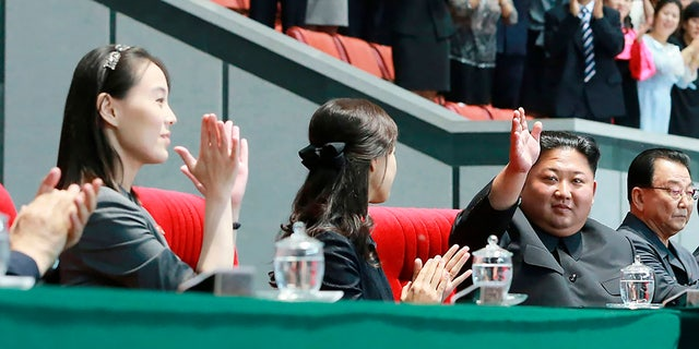 In this June 3, 2019, North Korean leader Kim Jong Un, second right, waves with his wife Ri Sol Ju, center, during the grand gymnastics and artistic performance at the May Day Stadium in Pyongyang. The woman next to Ri Sol Ju appears to be Kim's sister, Kim Yo Jong, who state media said attended the performance. (Korean Central News Agency/Korea News Service via AP)