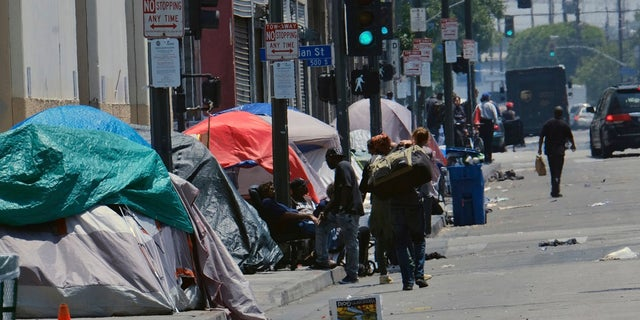 FILE - In this May 30, 2019 file photo tents housing homeless line a street in downtown Los Angeles. (AP Photo/Richard Vogel,File)