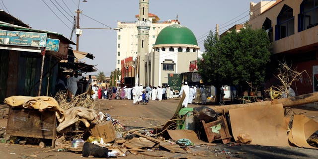 Worshipers gather at a mosque behind a roadblock set by protesters on a main street in the Sudanese capital Khartoum to stop military vehicles from driving through the area on Wednesday, June 5, 2019.