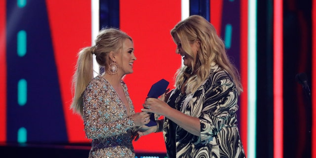 Carrie Underwood, left, accepts the award for female video of the year from presenter Trisha Yearwood at the CMT Music Awards on Wednesday, June 5, 2019, at the Bridgestone Arena in Nashville, Tenn.