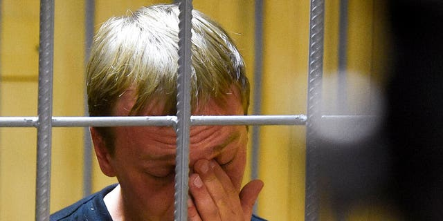 Ivan Golunov, a journalist who worked for the independent website Meduza, reacts in a cage in a court room in Moscow, Russia,