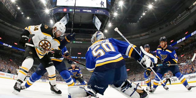 St. Louis Blues goaltender Jordan Binnington (50) catches the puck as Boston Bruins left wing Jake DeBrusk (74) watches for the rebound.