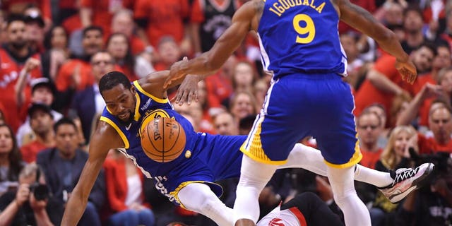 Golden State Warriors forward Kevin Durant, left, falls over Toronto Raptors center Serge Ibaka, bottom, as Warriors forward Andre Iguodala (9) looks on during first-half basketball game action in Game 5.