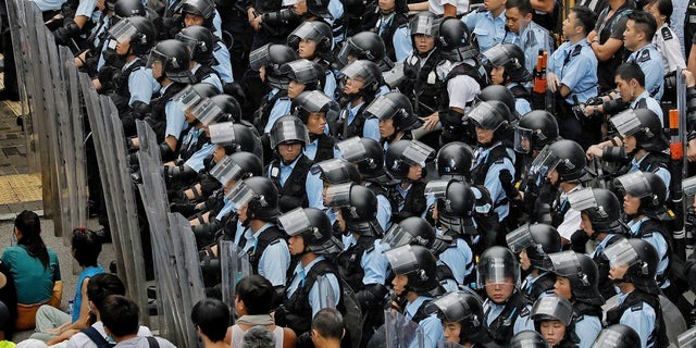 Policemen in anti-riot gear stand watch as the protesters gather outside the Legislative Council in Hong Kong, Wednesday, June 12, 2019. Government officials in Hong Kong are bracing for a showdown as protesters and police continue to face off into the early morning hours outside the semiautonomous Chinese territory's legislature ahead of Wednesday's debate over changes allowing extradition to the Chinese mainland. (AP Photo/Vincent Yu)