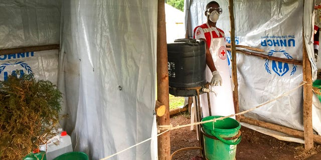 This photo taken Monday, June 10, 2019 and released by the International Rescue Committee (IRC), shows an Ebola screening checkpoint where people crossing from Congo go through foot and hand washing with a chlorine solution and have their temperature taken, at the Bunagana border crossing with Congo, in western Uganda.