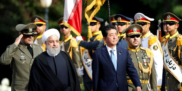 Japanese Prime Minister Shinzo Abe, center, reviews an honor guard as he is welcomed by Iranian President Hassan Rouhani, left, in an official arrival ceremony at the Saadabad Palace in Tehran.