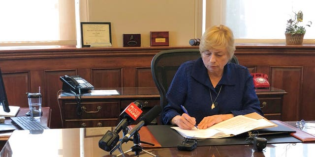 Maine Gov. Janet Mills signs a bill Wednesday that makes hers the eighth state to allow terminally ill people to end their lives with prescribed medication. (AP Photo/Marina Villeneuve)