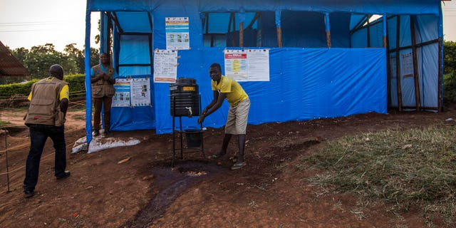 This photo released by the International Rescue Committee (IRC) shows a Congolese refugee boy washing his hands before entering one of the medical tents used for evaluating newly arrived Congolese for potential symptoms of Ebola, at the Kyaka refugee settlement in western Uganda Wednesday, June 12, 2019.