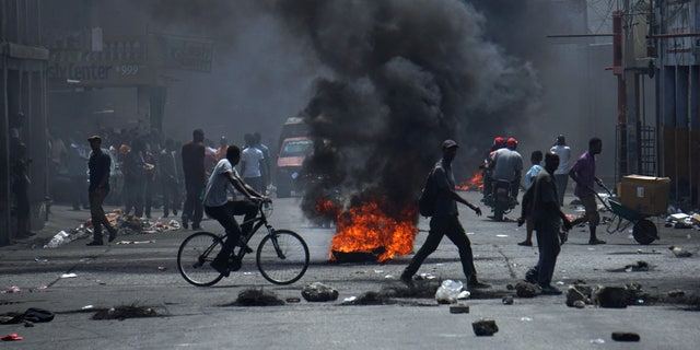 Tires that were set on fire by anti-government protesters burn in Haiti this month. (AP Photo/Edris Fortune)