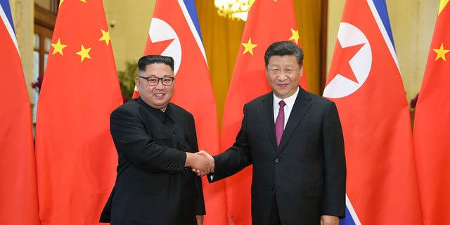 FILE - In this June 19, 2018, file photo released by China's Xinhua News Agency, Chinese President Xi Jinping, right, poses with North Korean leader Kim Jong Un for a photo during a welcome ceremony at the Great Hall of the People in Beijing. (Ju Peng/Xinhua via AP, File)