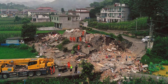 Rescue workers search for trapped people at a collapsed building after an earthquake in Shuanghe Town in Changning County of Yibin City, southwest China's Sichuan Province on Tuesday.