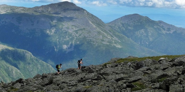 In this July 27, 2016, file photo, a pair of hikers traverse a trail on Mount Washington. (AP Photo/Jim Cole, File)