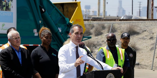Los Angeles Mayor Eric Garcetti, at podium, surrounded by city sanitation workers, speaks about the city's homelessness problem at a news conference in Los Angeles on June 19, 2019. Far left, is city councilman, Mike Bonin. (AP Photo/Damian Dovarganes)