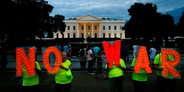 "Protesters hold signs spelling out, ""No War,"" outside the White House, Thursday June 20, 2019, in Washington, after President Donald Trump tweeted that ""Iran made a very big mistake"" by shooting down a U.S. surveillance drone over the Strait of Hormuz in Iran."