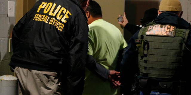 In this Oct. 22, 2018, file photo, U.S. Immigration and Customs Enforcement agents escort a target to lockup during a raid in Richmond, Va. Carrying out President Donald Trump's hard-line immigration policies has exposed ICE to unprecedented public scrutiny and criticism. (AP Photo/Steve Helber, File)