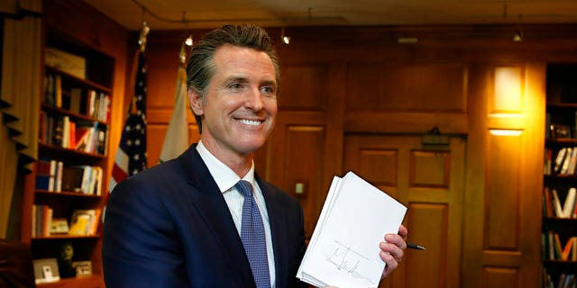 Gov. Gavin Newsom holds up he $215 billion 2019-2020 state budget he signed in Sacramento, Calif., Thursday, June 27, 2019. This is Newsom's first state budget since becoming governor. (AP Photo/Rich Pedroncelli)