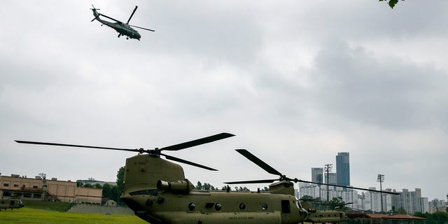 The Marine One helicopter, top, carrying President Donald Trump to the demilitarized zone (DMZ) takes off from Seoul, South Korea, Sunday, June 30, 2019, as a staff helicopter prepares en route to the DMZ. (Associated Press)