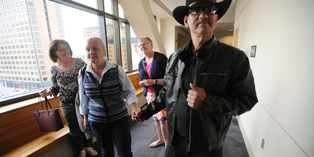 Timothy Hoffman, right, father of slain teenager Cynthia Hoffman receives support from Edie Grunwald, left, who's son David Grunwald was murdered in Nov. 2016, as they entered a Superior courtroom for the arraignment of Cynthia's murder suspects in the Nesbett Courthouse on Tuesday, June 18, 2019 in Anchorage, Alaska. (Bill Roth/Anchorage Daily News via AP)
