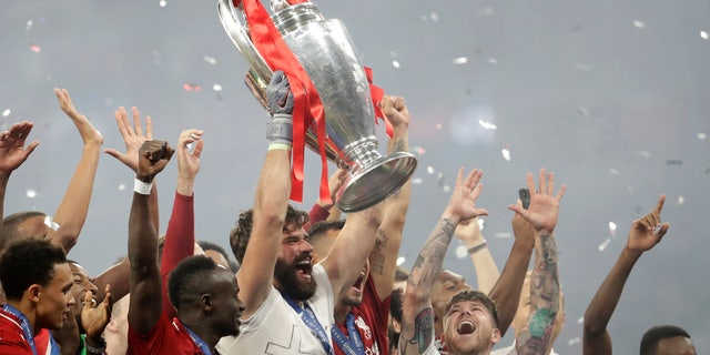 Liverpool's goalkeeper Alisson lifts the trophy as celebrates with his teammates after winning the Champions League final soccer match between Tottenham Hotspur and Liverpool at the Wanda Metropolitano Stadium in Madrid, Sunday, June 2, 2019. Liverpool won 2-0. (AP Photo/Felipe Dana)