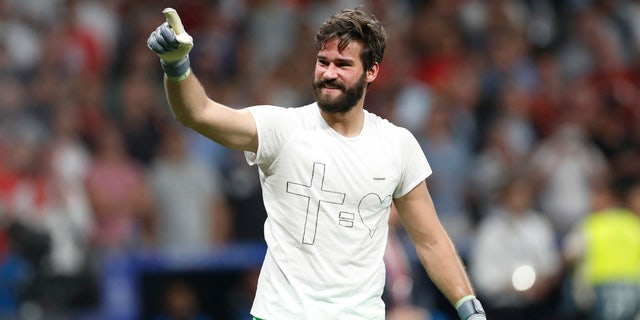 Liverpool goalkeeper Alisson celebrates at the end of the Champions League final soccer match between Tottenham Hotspur and Liverpool at the Wanda Metropolitano Stadium in Madrid, Saturday, June 1, 2019. (AP Photo/Bernat Armangue)